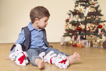 Two year old boy with christmas tree and toys