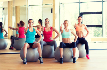 group of smiling women showing thumbs up in gym