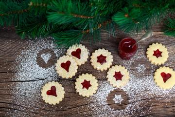 Weihnachtsplätzchen mit Himbeerkonfitüre auf einem Holztisch
