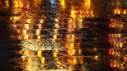 Karussel spiegelt sich in nasser Strasse