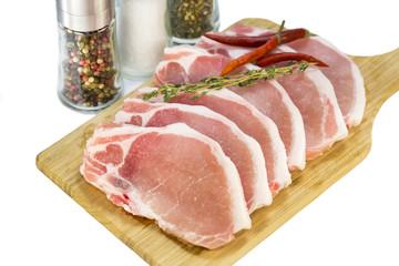 raw pork steaks on a cutting board
