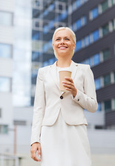 smiling businesswoman with paper cup outdoors