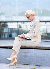 young smiling businesswoman with notepad outdoors
