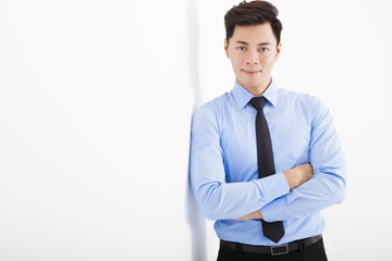 young businessman leaning against white wall in office