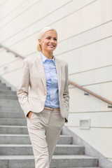 young smiling businesswoman walking down stairs