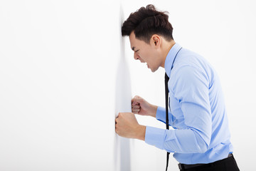 angry young business man  leaning at the wall in office