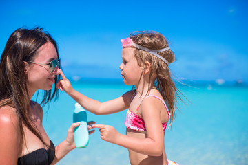 Little girl applying sunblock cream on her mom nose