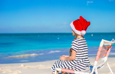 Little girl wearing Santa hat during tropical beach vacation