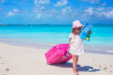 Little adorable girl with big suitcase on tropical vacation