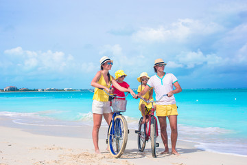 Young happy family riding bicycles on tropical beach