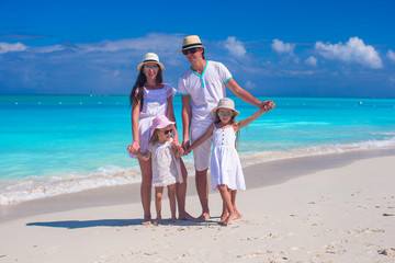 Family of four on caribbean beach summer vacation