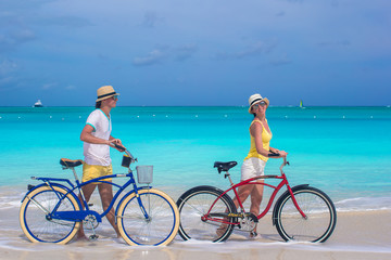 Happy couple riding bikes during tropical vacation