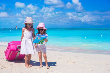 Little girls with big suitcase and map searching for the way on