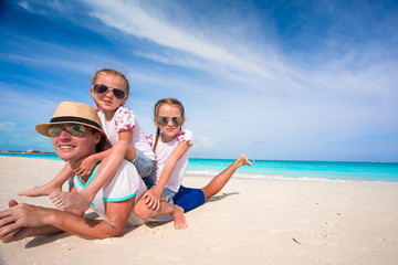 Happy father and adorable little daughters at tropical beach