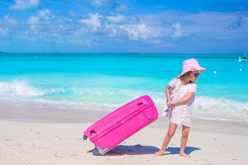 Little adorable girl with big suitcase on tropical beach