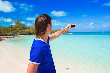 Young man with phone on tropical caribbean beach