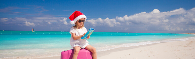 Little girl in Santa hat sitting on large suitcase at tropical