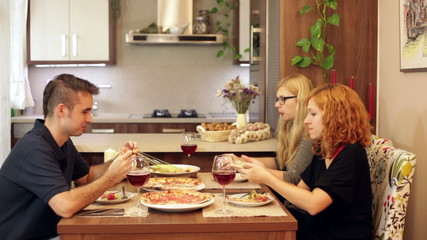 Group of friends eating pizza in dining room at home.