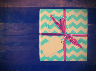Festive gift box with chevron stripe wrapping on wood