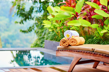 Towels with frangipani flowers in Balinese spa