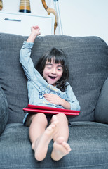 Happy girl smiling while playing with tablet on the home armchai