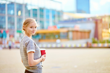 Girl drinking coffee at La Defense in Paris