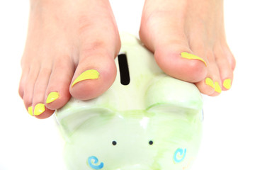 women feet (pedicure)  with coin bank