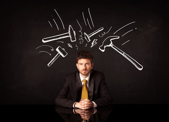 Depressed businessman sitting under hammer marks