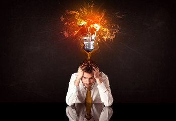 Businessman sitting under a blowing idea bulb