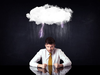 Depressed businessman sitting under a cloud