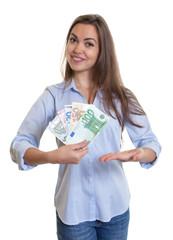 Frau mit langen braunen Haaren zeigt Geldscheine