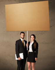 Business couple with blank cardboard