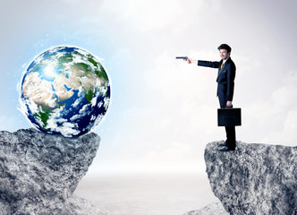 Businessman on rock mountain with a globe