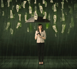 Businesswoman standing with umbrella in dollar bill rain concept