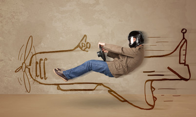 Funny pilot driving a hand drawn airplane on the wall