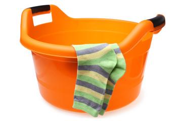 Orange plastic wash bowl with striped socks