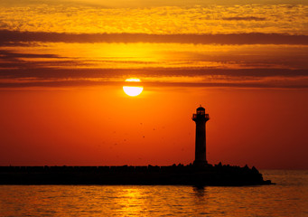 Silhouette of a lighthouse at sunrise