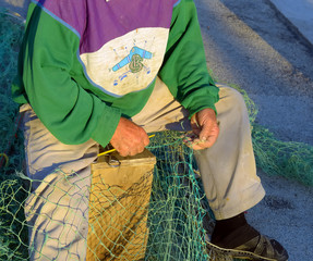 Fisherman is repairing the fishnet.