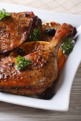 fried duck leg with oranges on a white plate, vertical