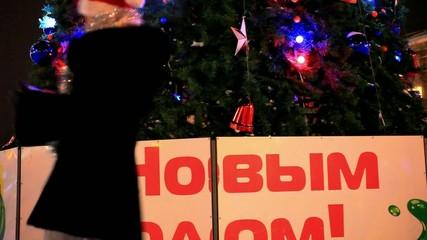 Beautiful woman in fur coat and santa hat near christmas tree