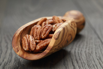 dried pecan nuts in olive scoop on wood table
