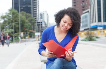 Lesende Studentin aus Südamerika in der Stadt