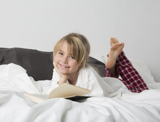 Smiling Young Girl Reading a book