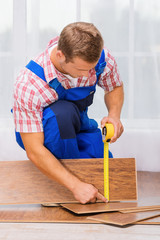 Repairman measuring wood block