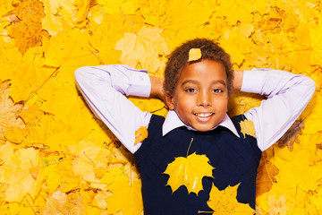 happy little black boy in autumn maple leaves