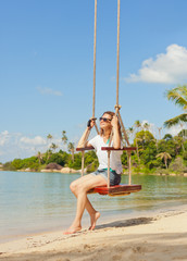 beautiful girl on a swing against the background tropical seasca