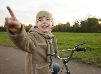 little cute boy outside in park near carousel on bicycle