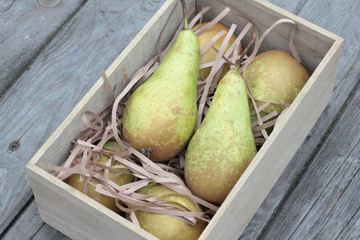 Wooden box of fresh pears on timber planks.