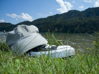 cap and shoes by the lake