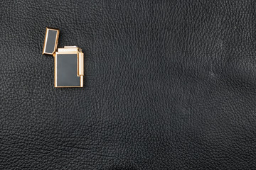 Gold Lighter lies on natural leather